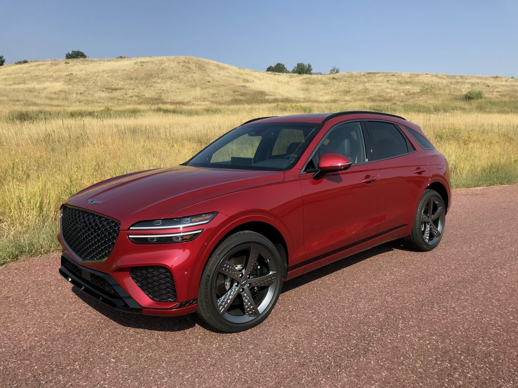 The red GV70 sits in an open green field and is positioned in a three-quarter shot for our 2022 Genesis GV70 review
