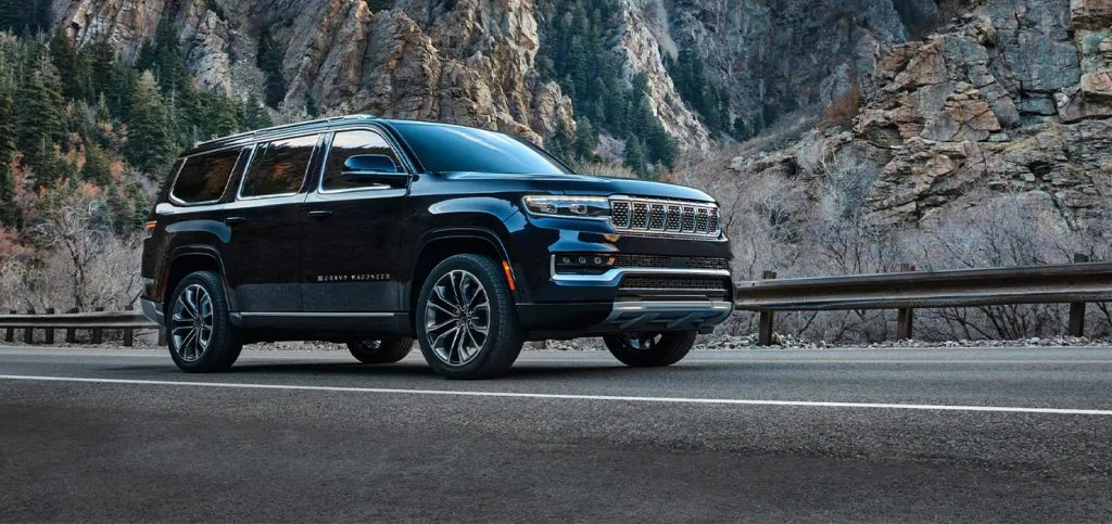 A black 2022 Jeep Grand Wagoneer driving by the mountains.