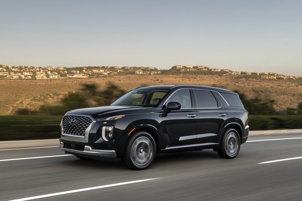 A black 2022 Hyundai Palisade travels on a highway past arid rolling hills on a sunny day