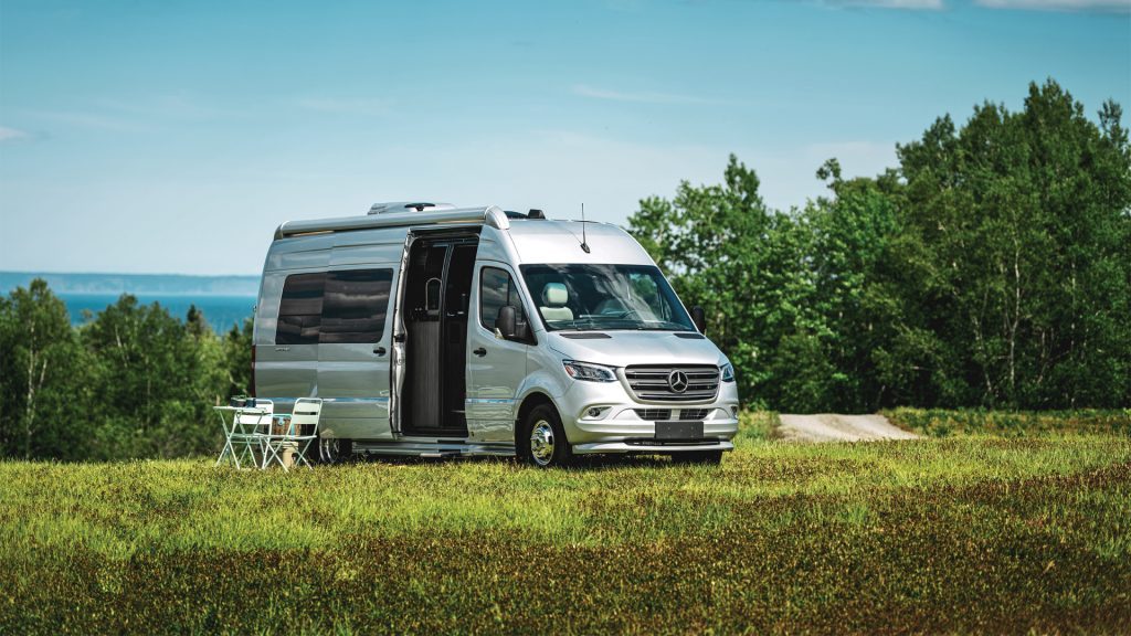 Airstream 24GL is parked in a lovely field with a table and chair set up. This is one of the best small RVs for couples