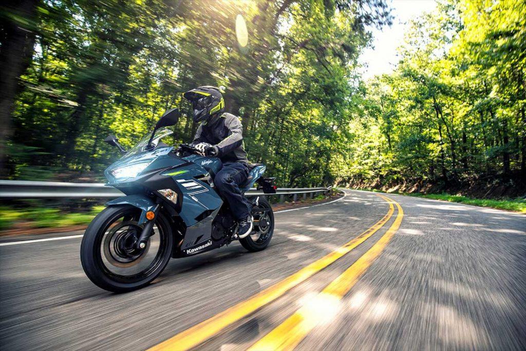 A rider on a dark-blue 2022 Kawasaki Ninja 400 ABS riding on a forest road