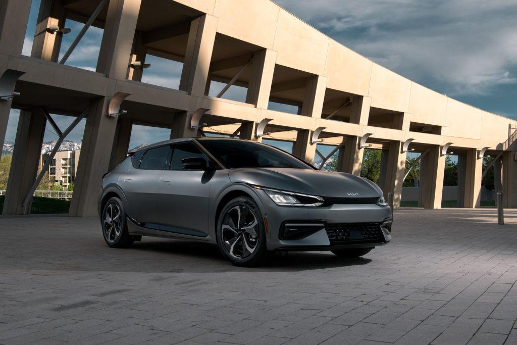 The 2022 Kia EV6 model in dark gray parked on a brick plaza