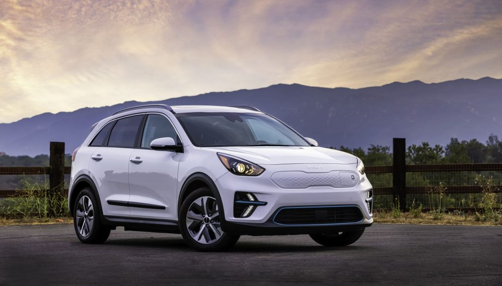 2022 Kia Niro EV in whit paint color parked by a barb wire wooden fence at sunset