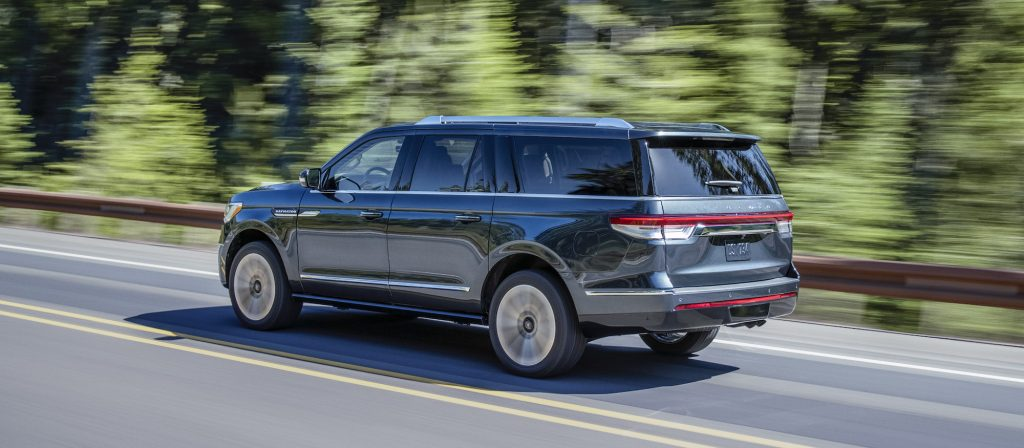 A dark-blue 2022 Lincoln Navigator SUV traveling on a highway past a blur of trees