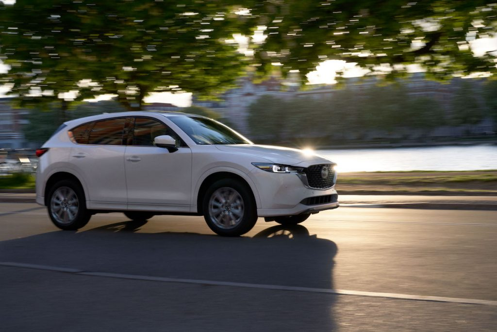 A white 2022 Mazda CX-5 2.5 Turbo Signature compact SUV travels on a road as the sun glints off the hood