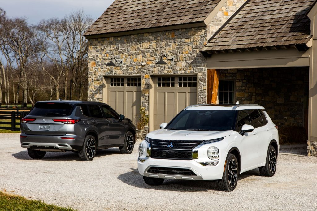 A white and black Mitsubishi Outlander sitting in front of a stone garage.