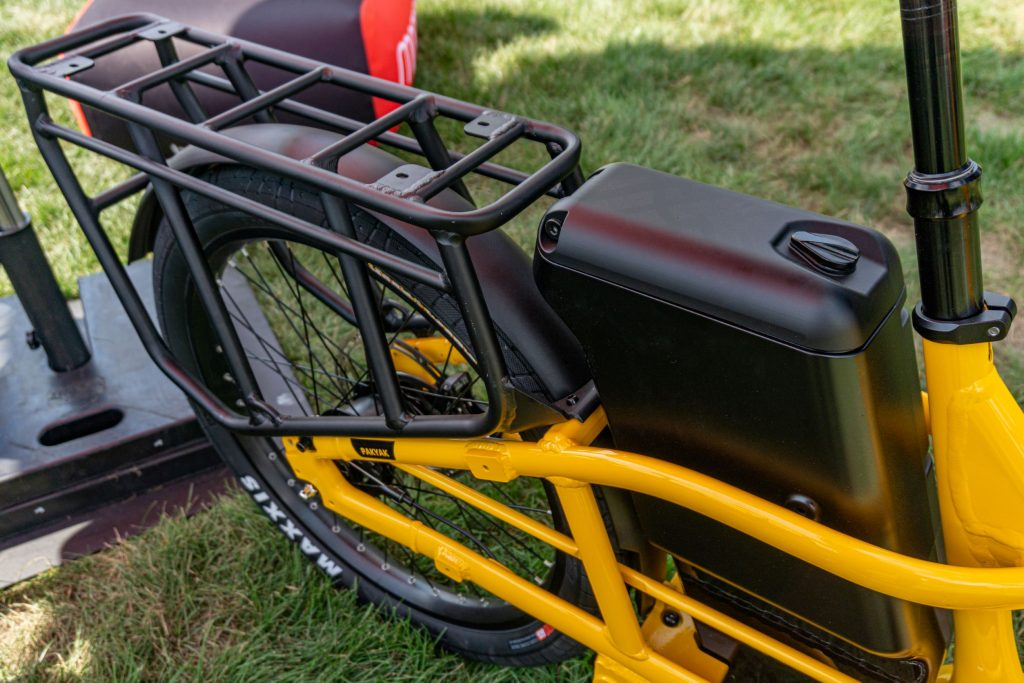 The black rear rack and lockable storage container on a yellow 2022 Momentum Pakyak E+