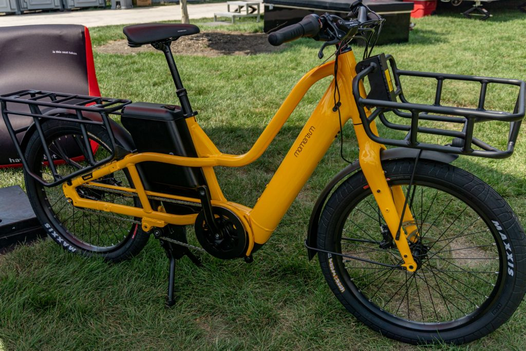 The right side view of a yellow-and-black 2022 Momentum Pakyak E+ under a canopy