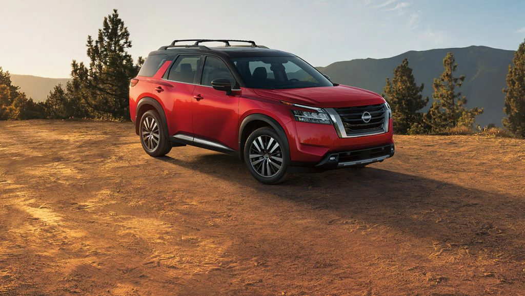 red 2022 nissan pathfinder parked outside on a dirt road