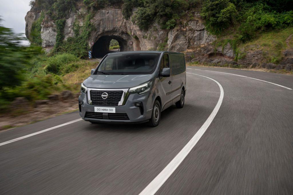 A gray 2022 Nissan Primastar drives down a road near a mountain