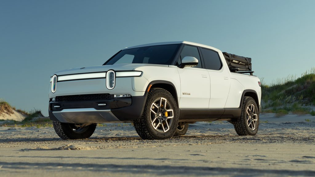 A white 2022 Rivian R1T parked in the sand on a beach