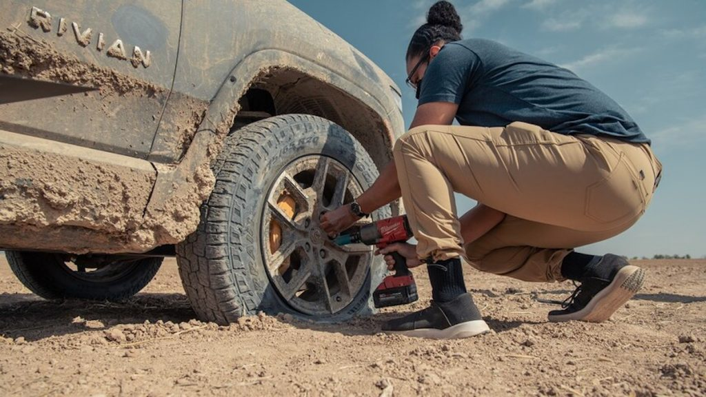A man fixing a flat tire on the Rivian R1T