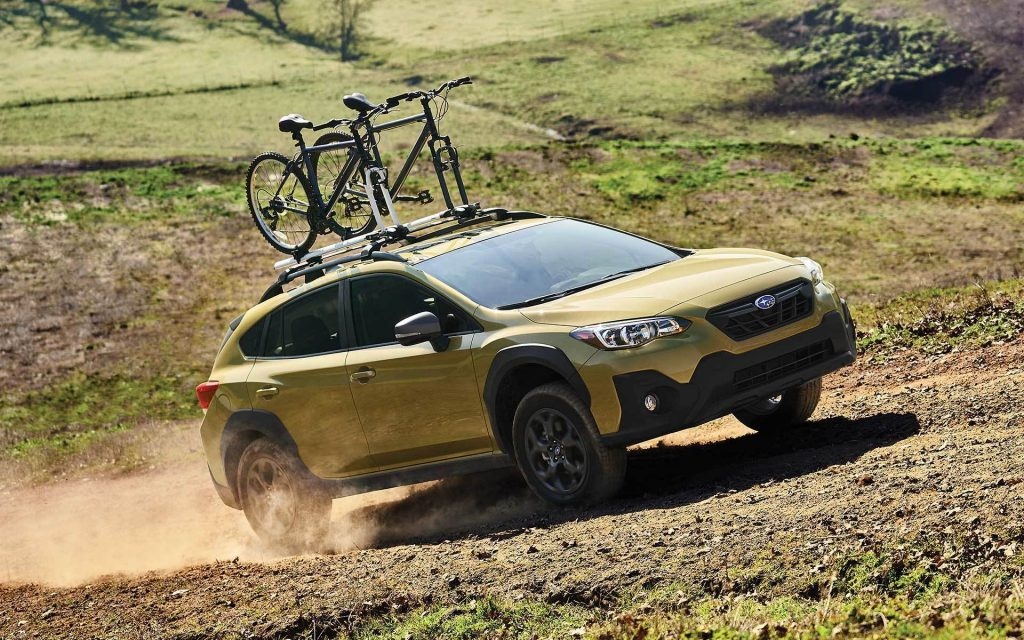 A yellow 2021 Subaru Crosstrek with a bike on top drives on a dirt road