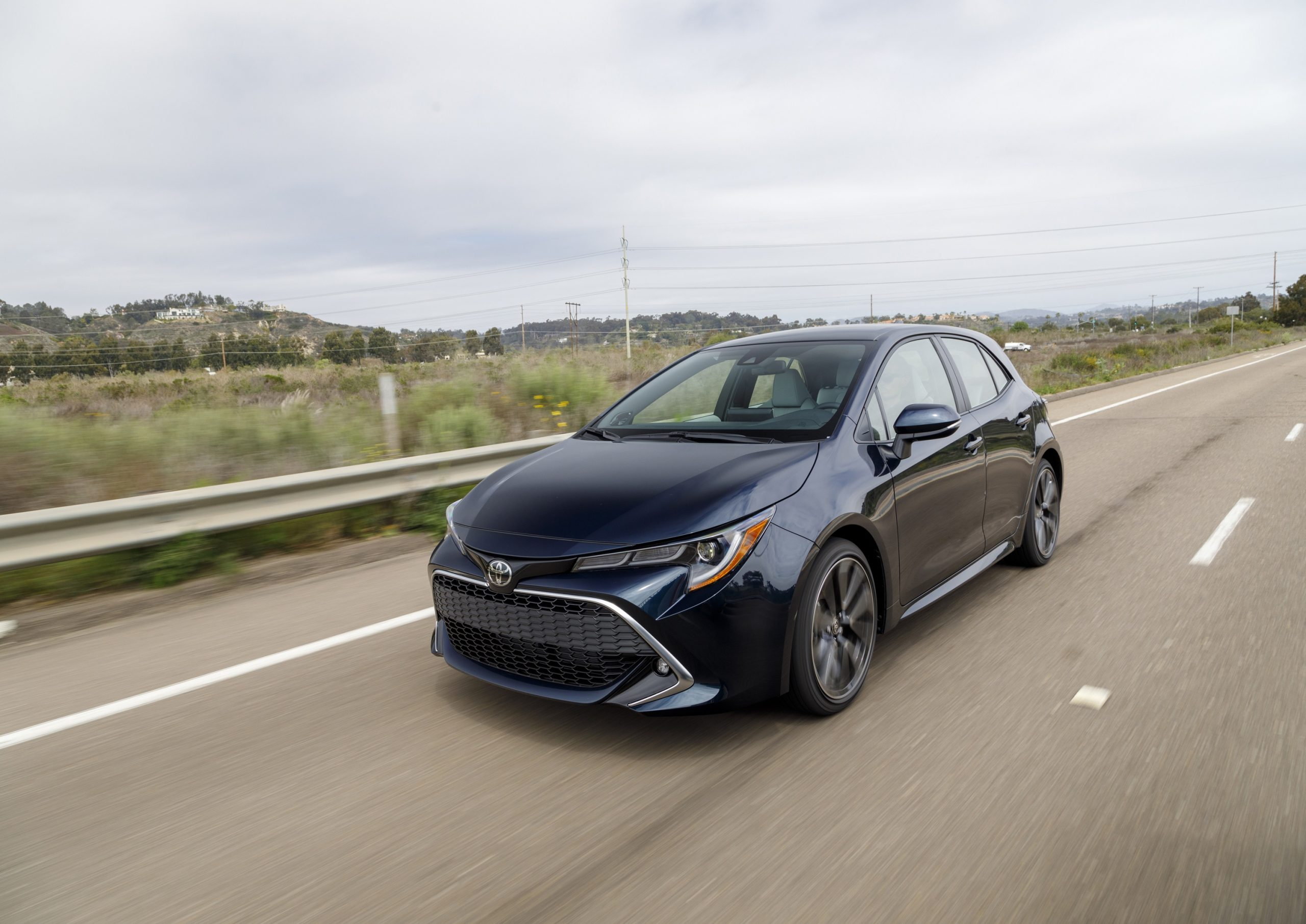 A blue 2022 Toyota Corolla hatchback shot from the front 3/4 while in motion