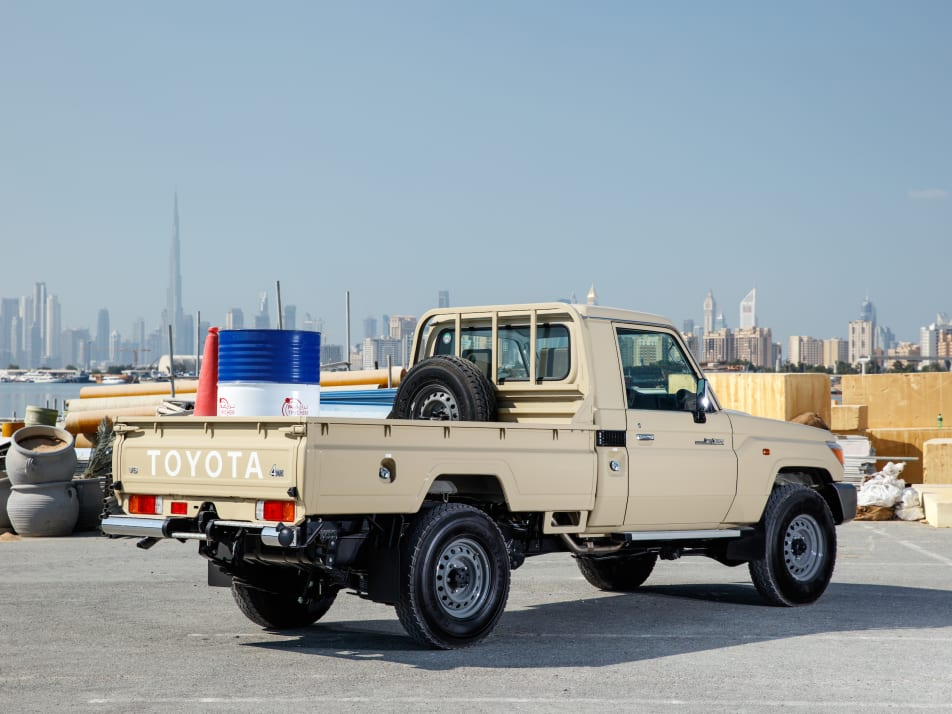 A tan 2022 Toyota LC70 pickup with cargo in the back parked outside