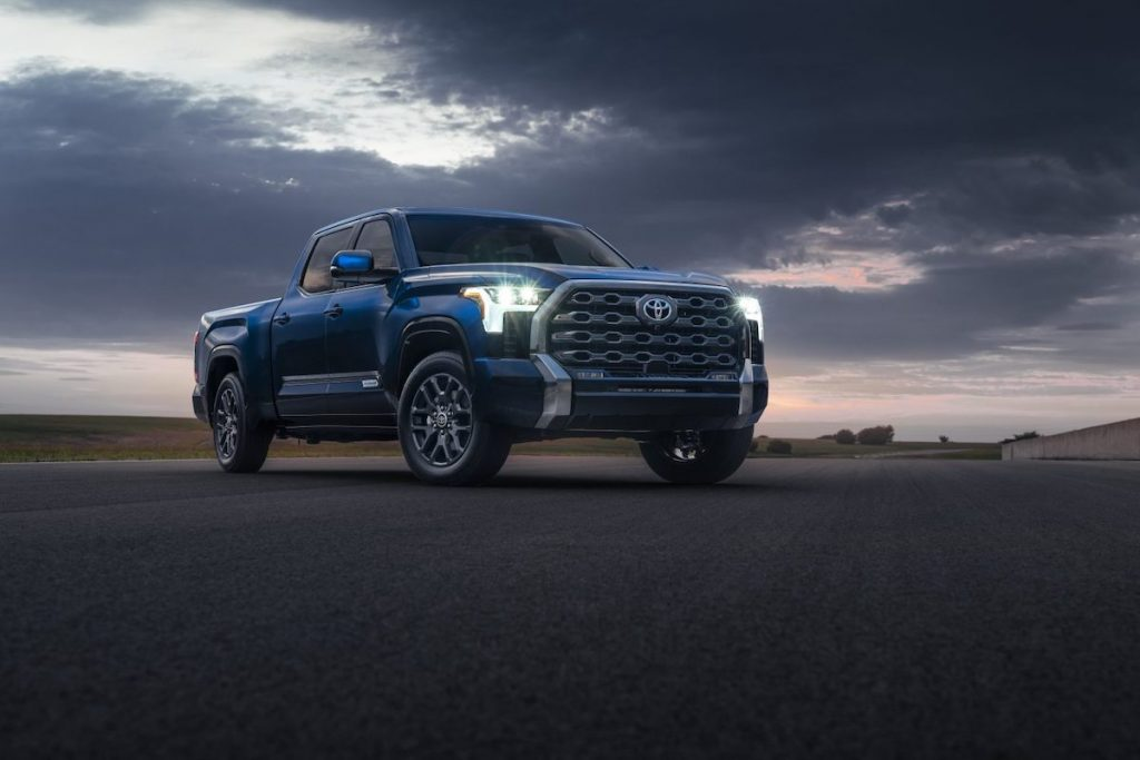 A blue 2022 Toyota Tundra Platinum pickup truck parked on the pavement under a cloudy sky