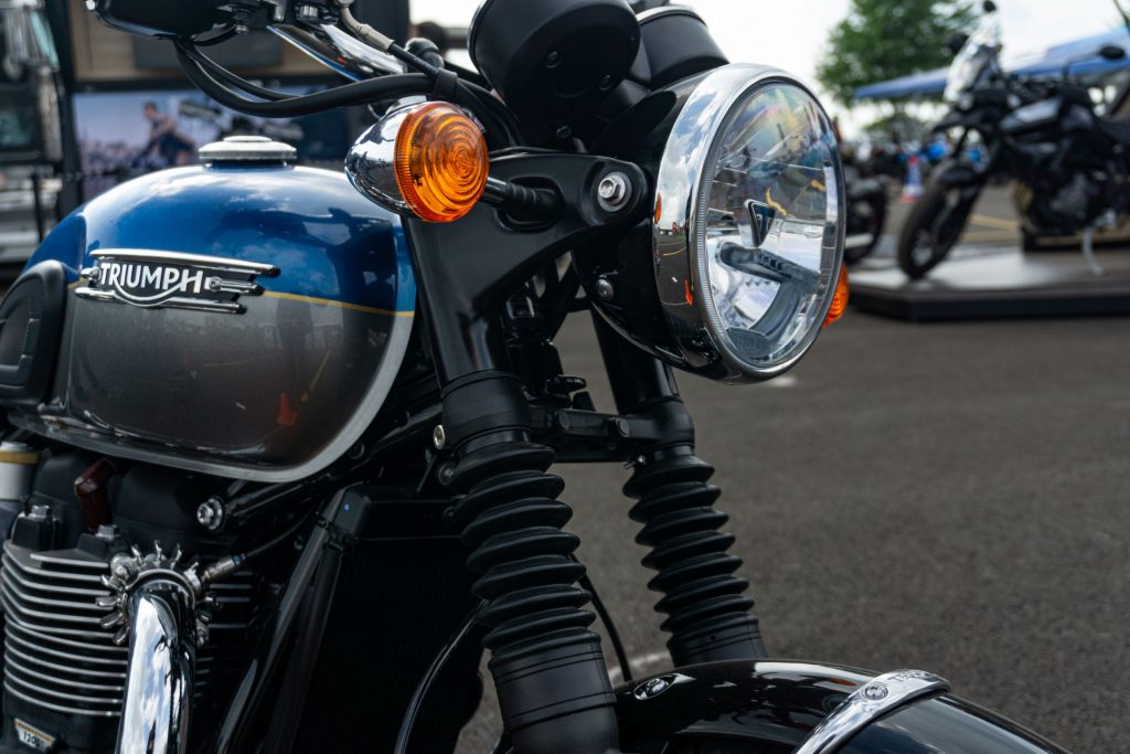 The headlight and forks of a blue-and-silver 2022 Triumph Bonneville T120