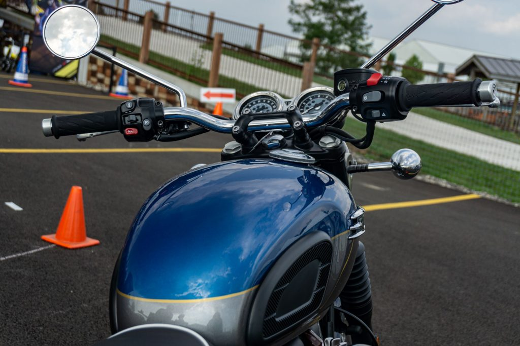 The rear view of a blue-and-silver 2022 Triumph Bonneville T120's fuel tank, handlebars, and gauges