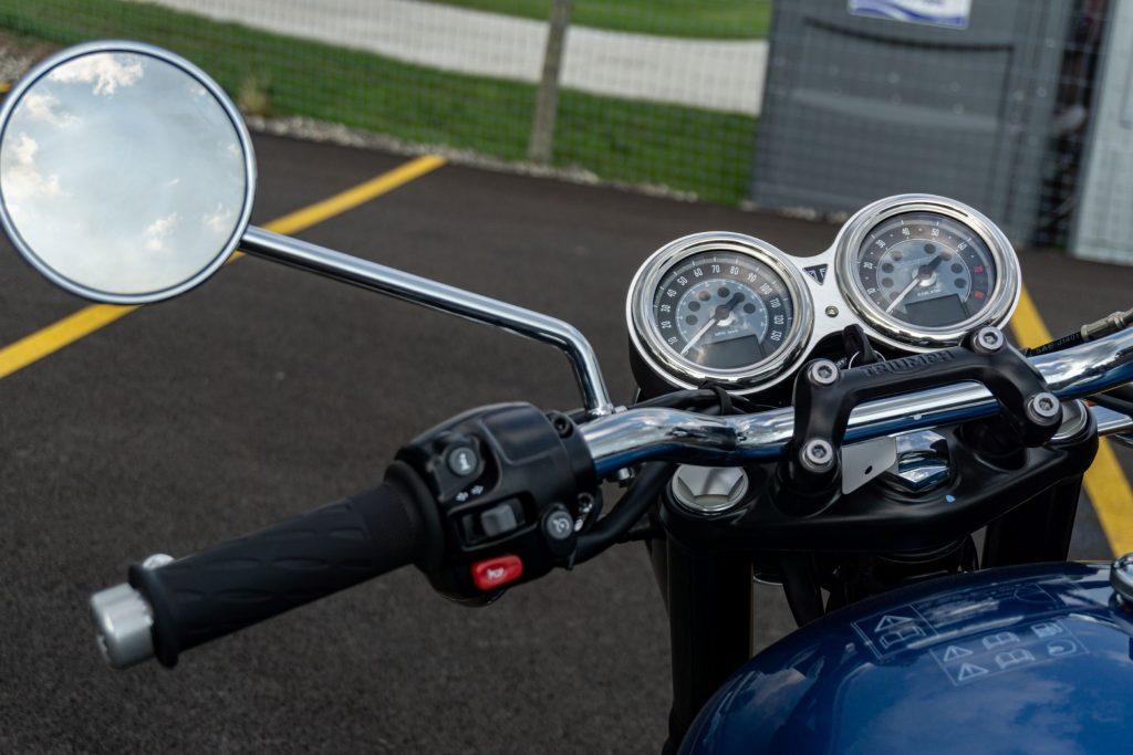 A close-up view of a blue-and-silver 2022 Triumph Bonneville T120's silver gauges