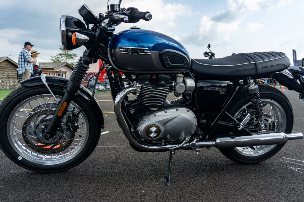 The left side of a blue-and-silver 2022 Triumph Bonneville T120 in a parking lot