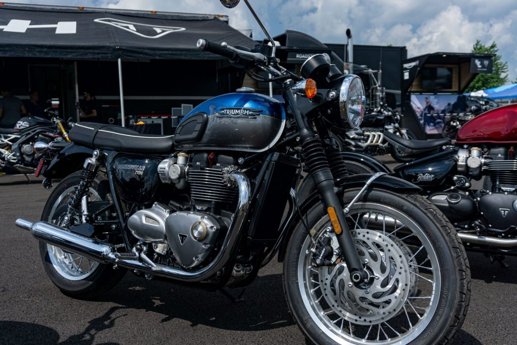 The side 3/4 view of a blue-and-silver 2022 Triumph Bonneville T120 in a parking lot