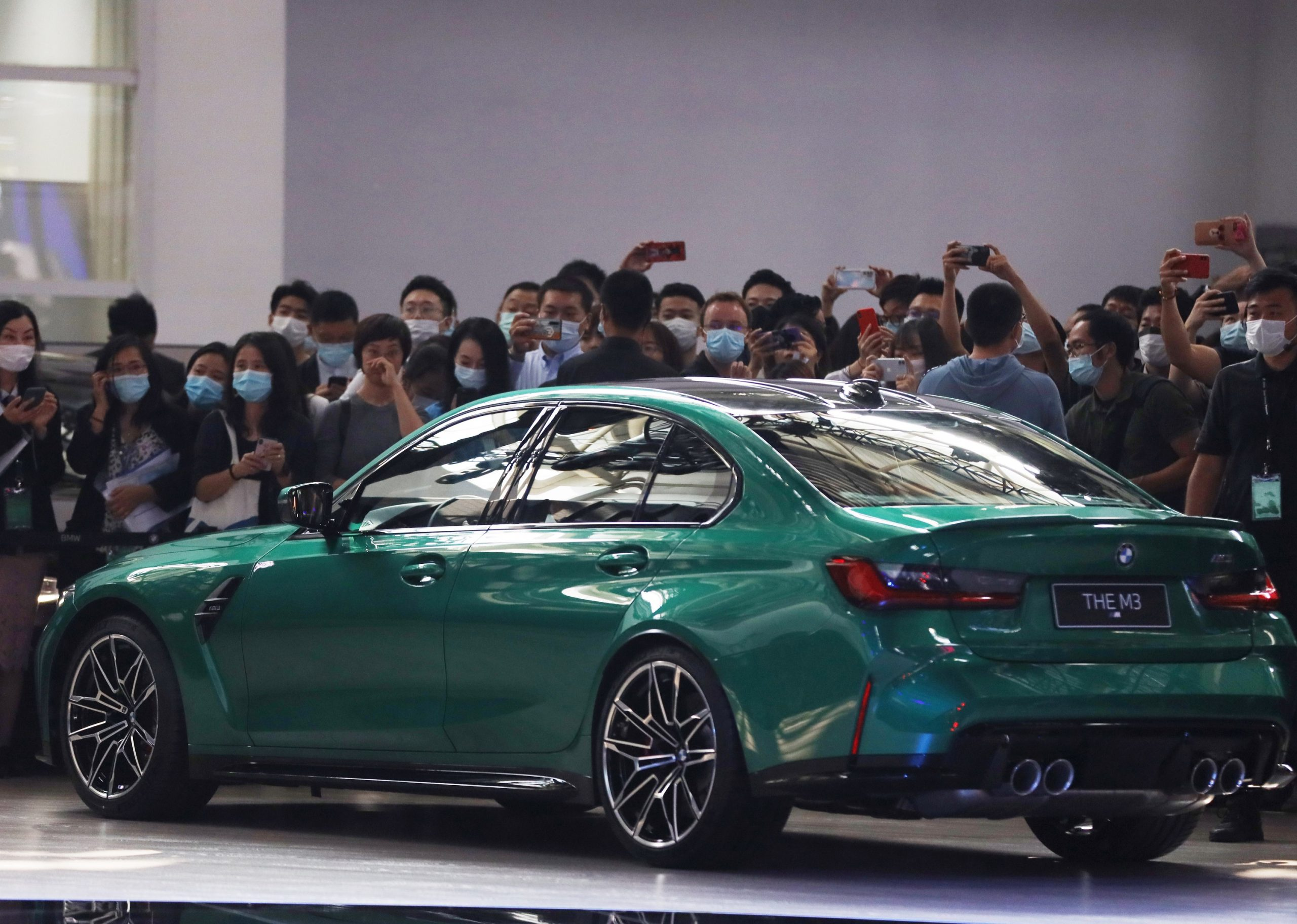An Isle of Man green BMW M3 at an auto show, shot from the rear 3/4 angle.