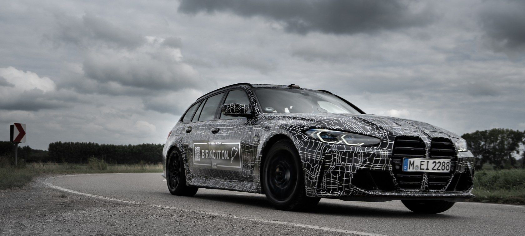 A BMW M3 Touring shows off the new BMW Kidney Grille while wrapped in camo, shot from the front 3/4