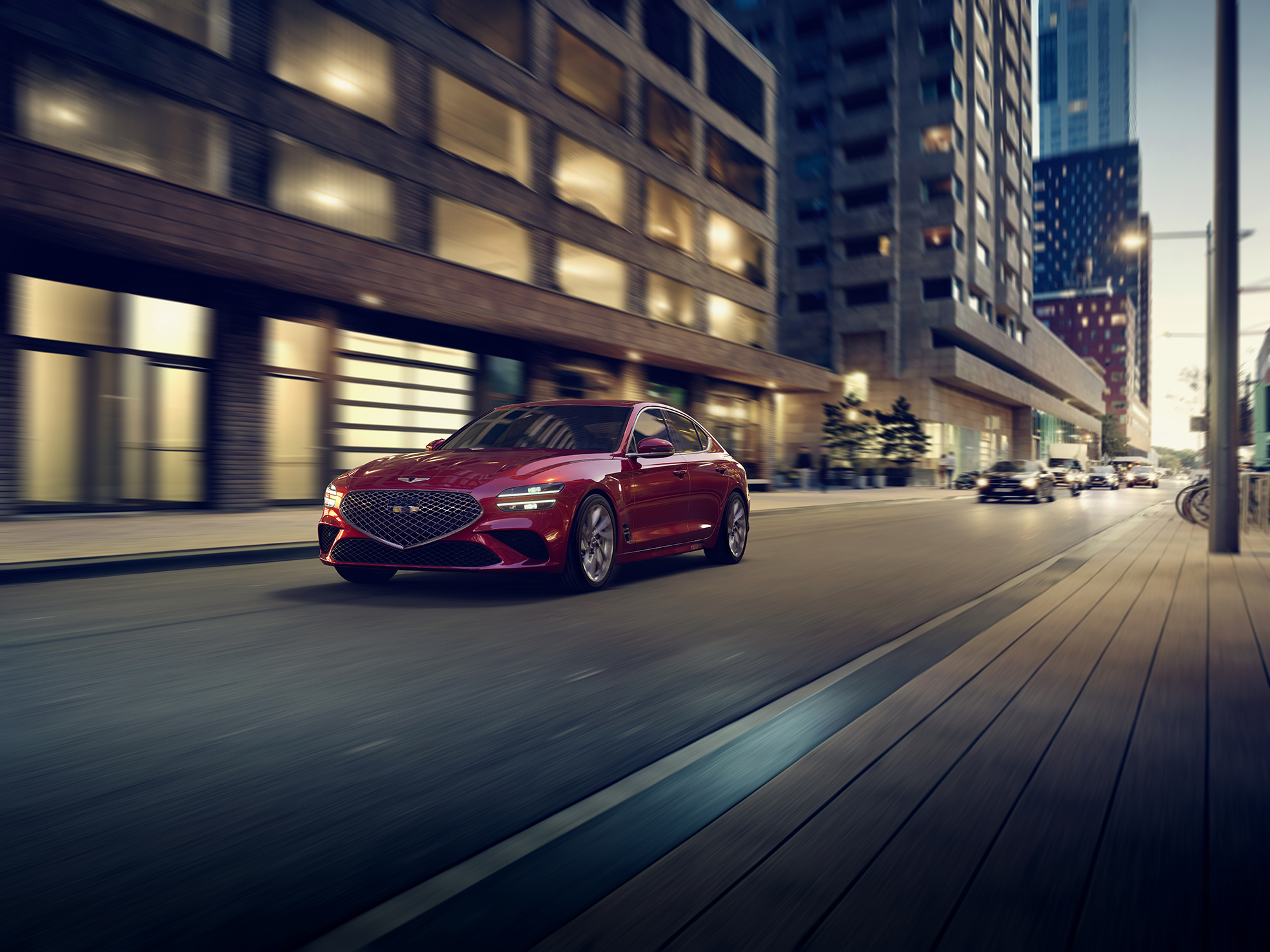 A red 2022 Genesis G70 rolling down a city street at night shot from the front 3/4