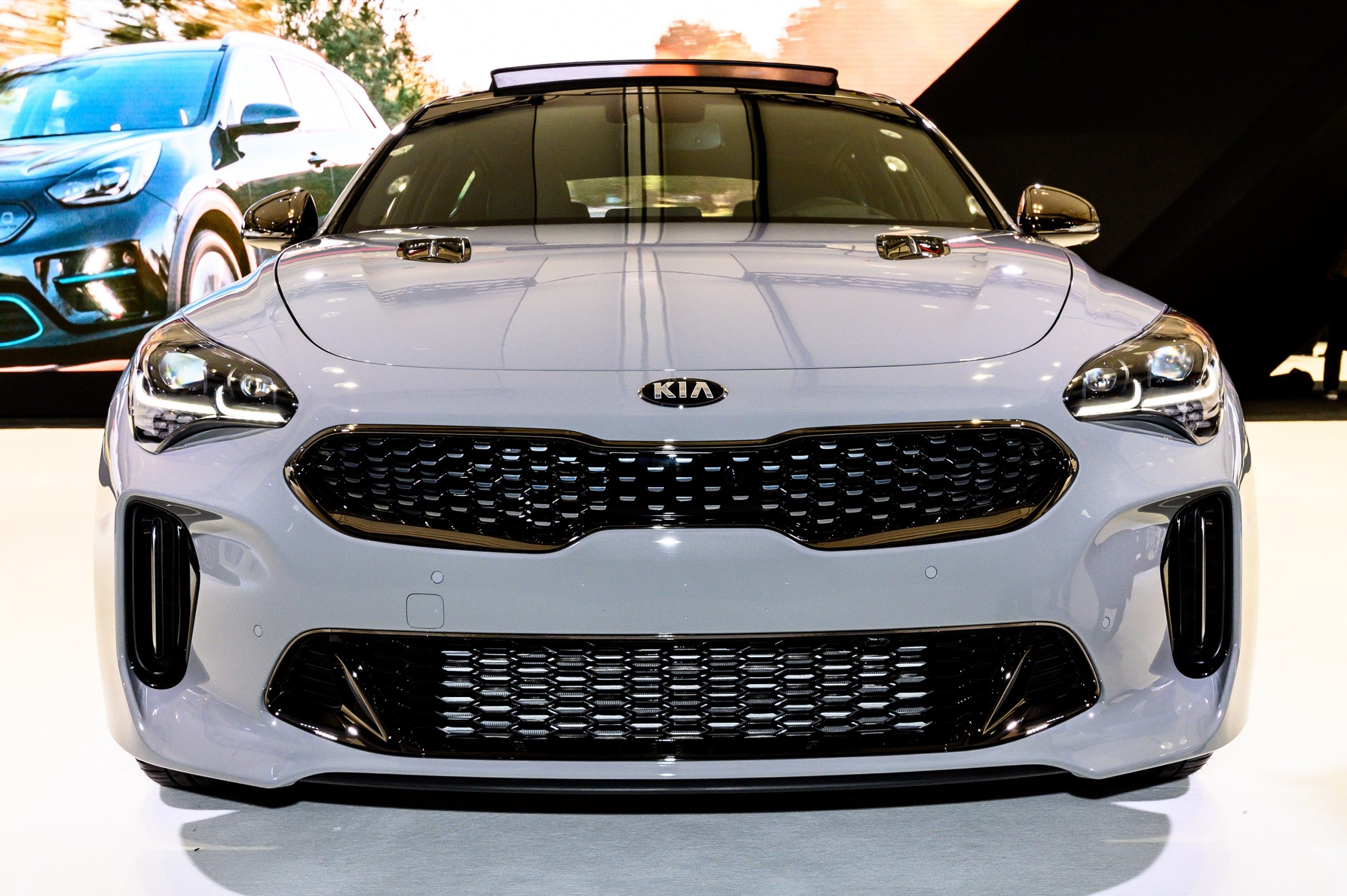 The 2022 Kia Stinger GT, shot from the front at an auto show in a pale grey paint