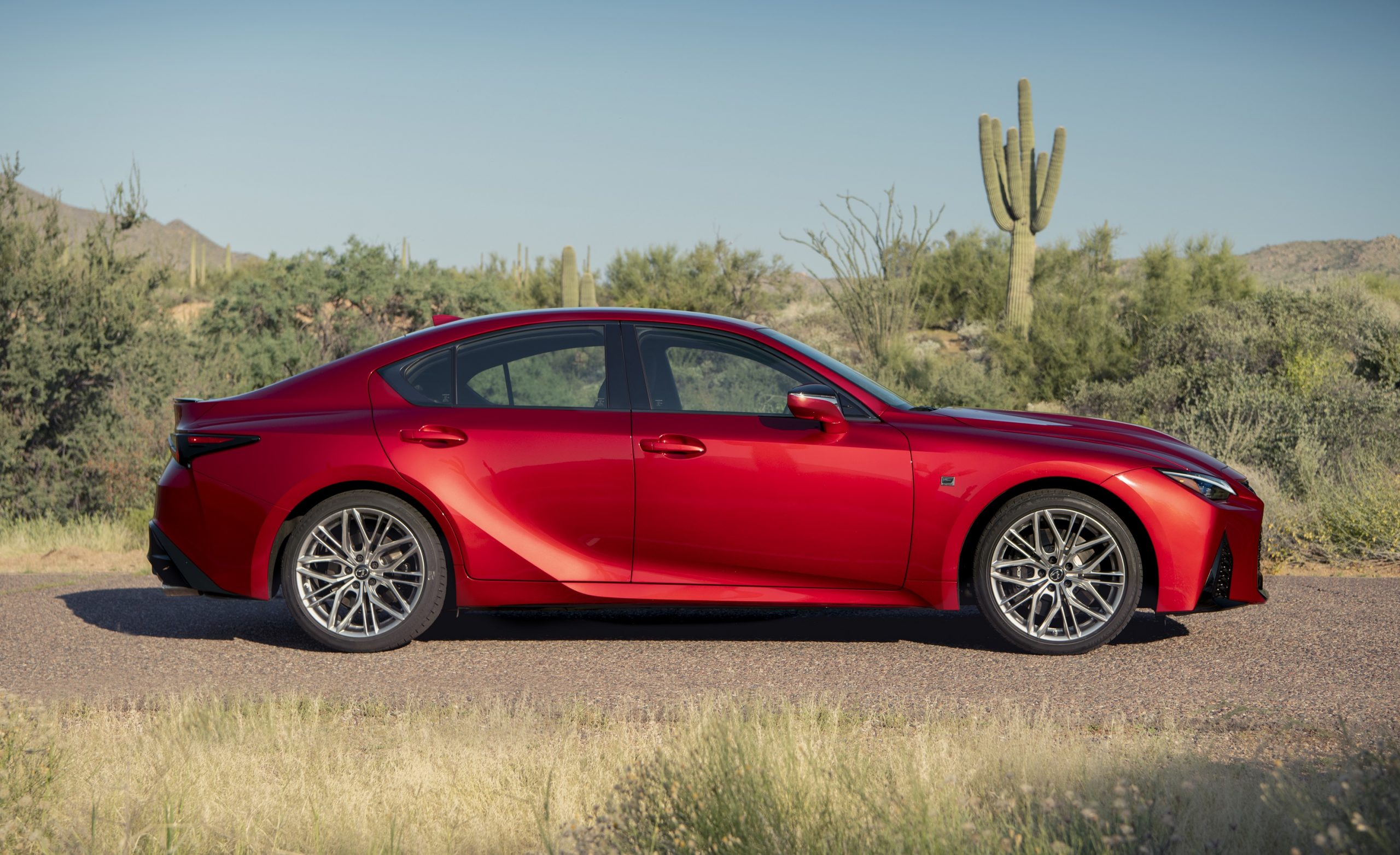 A red Lexus IS 500 shot in profile in the desert with cacti in the background