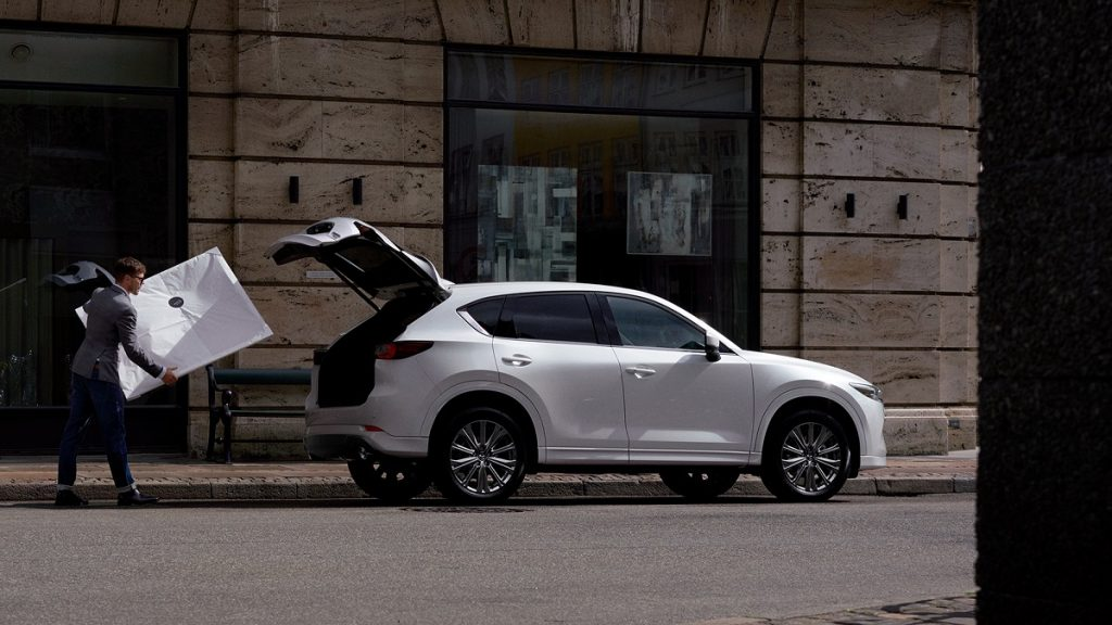 A man loading a large package into the trunk of a white 2022 Mazda CX-5.