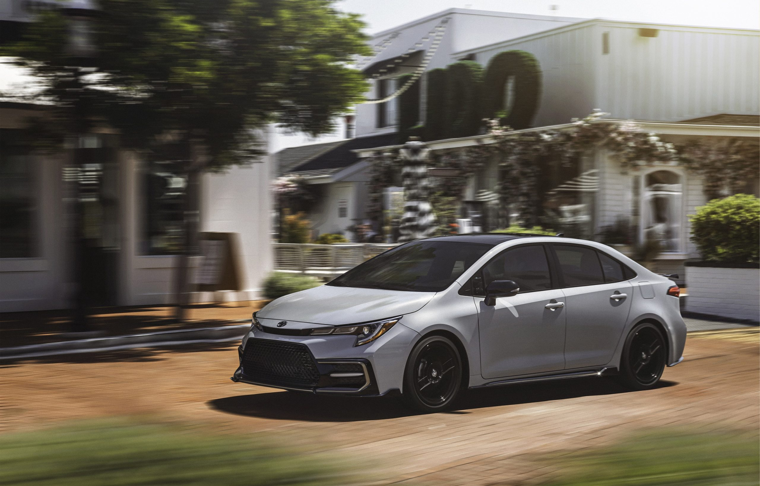 A grey 2022 Toyota Corolla Apex shot from the front 3/4 on a busy street