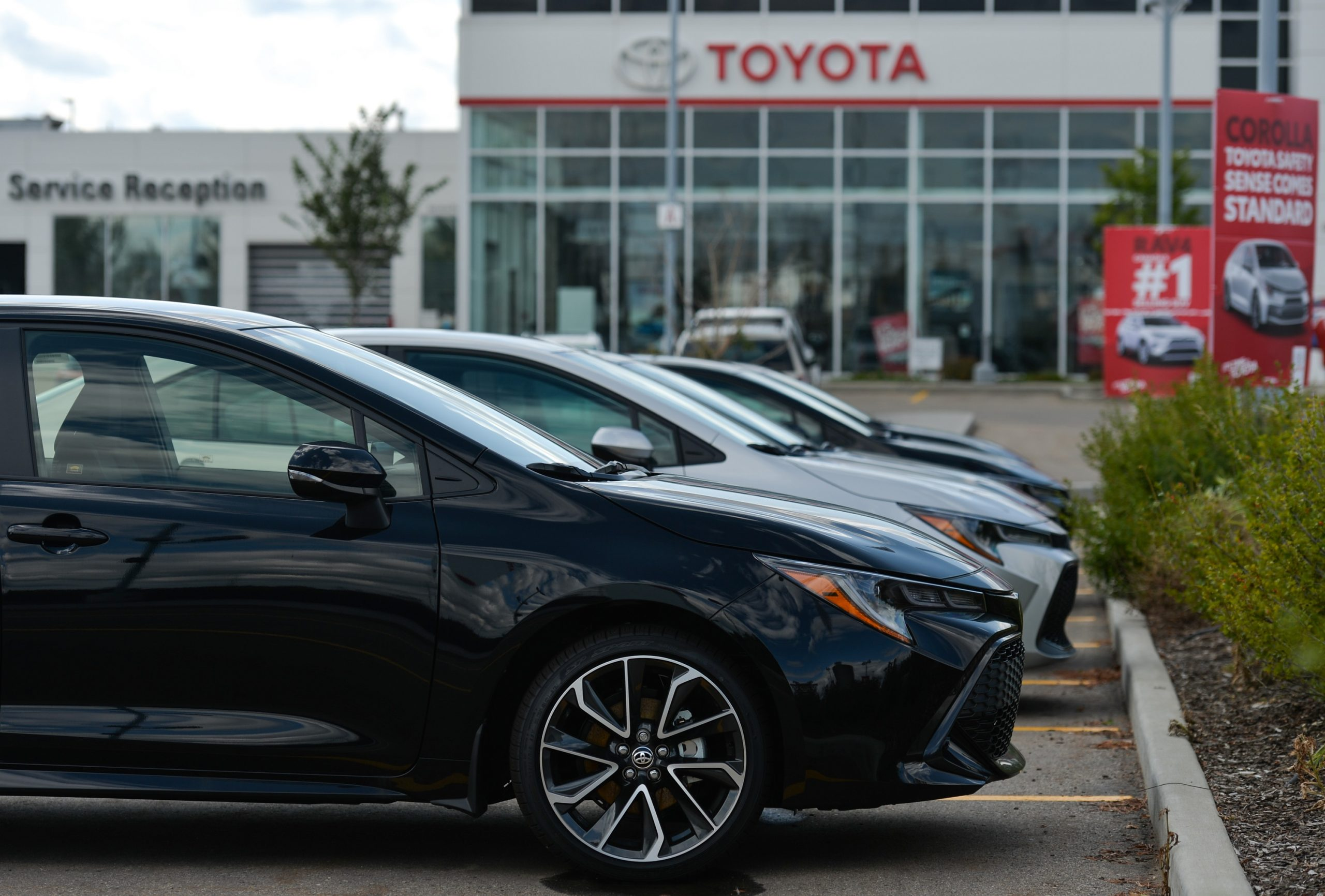 A line of 2022 Toyota Corolla models, shot in profile on a Toyota dealership lot