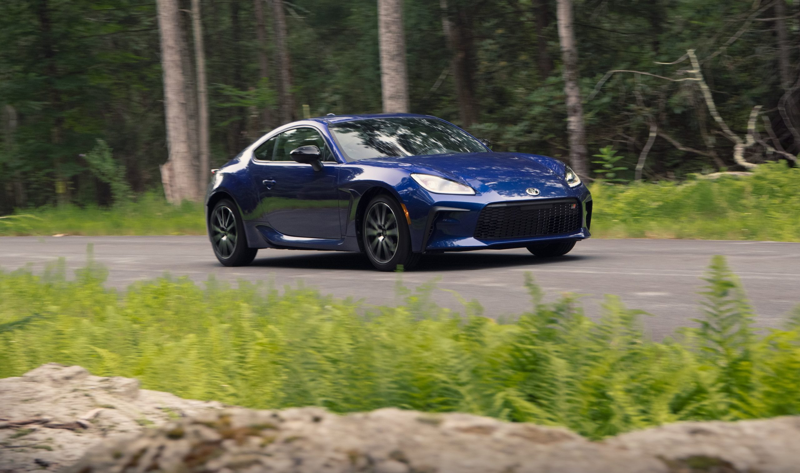 A dark blue 2022 Toyota GR 86 rolls down a forest road, shot from the front 3/4
