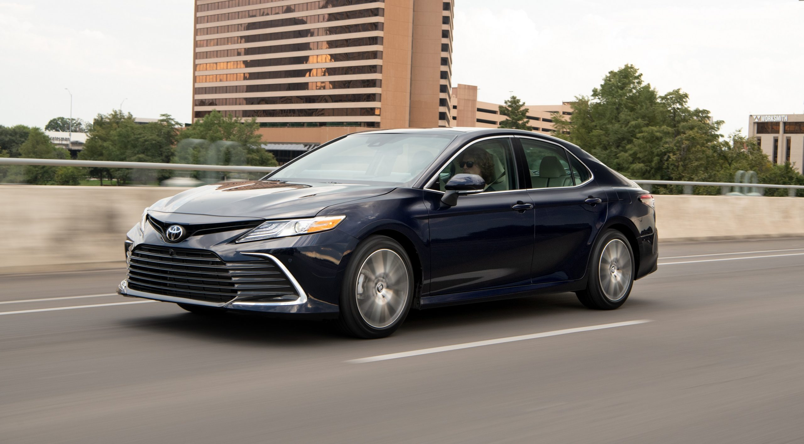 A blue 2021 Toyota Camry sedan rolls down the highway, shot from the front 3/4 angle.