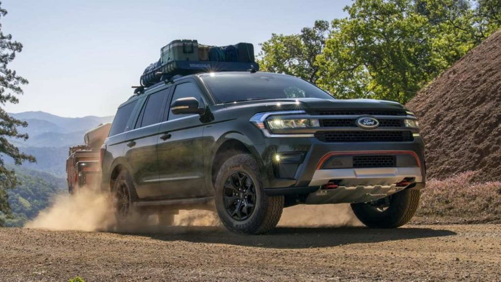 Green 2022 Ford Expedition Timberline drives down a dirt road with cargo on board