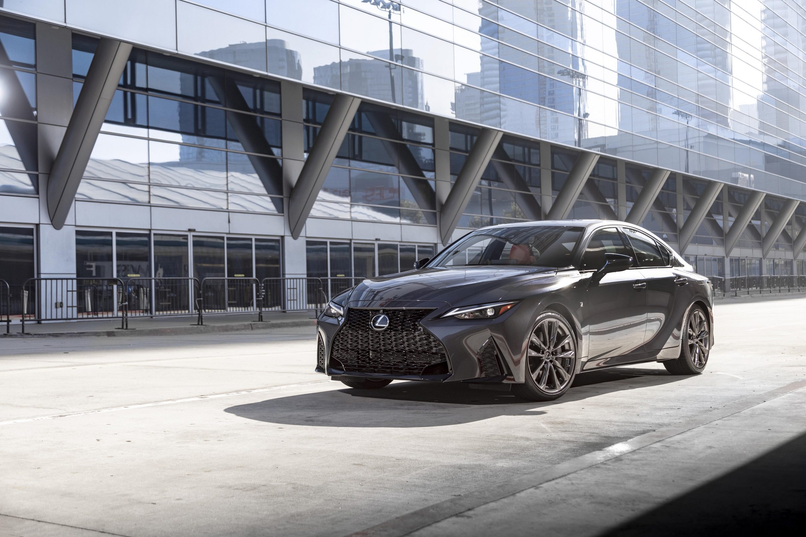 A grey 2022 Lexus IS sedan shot from the front 3/4 on an empty city street