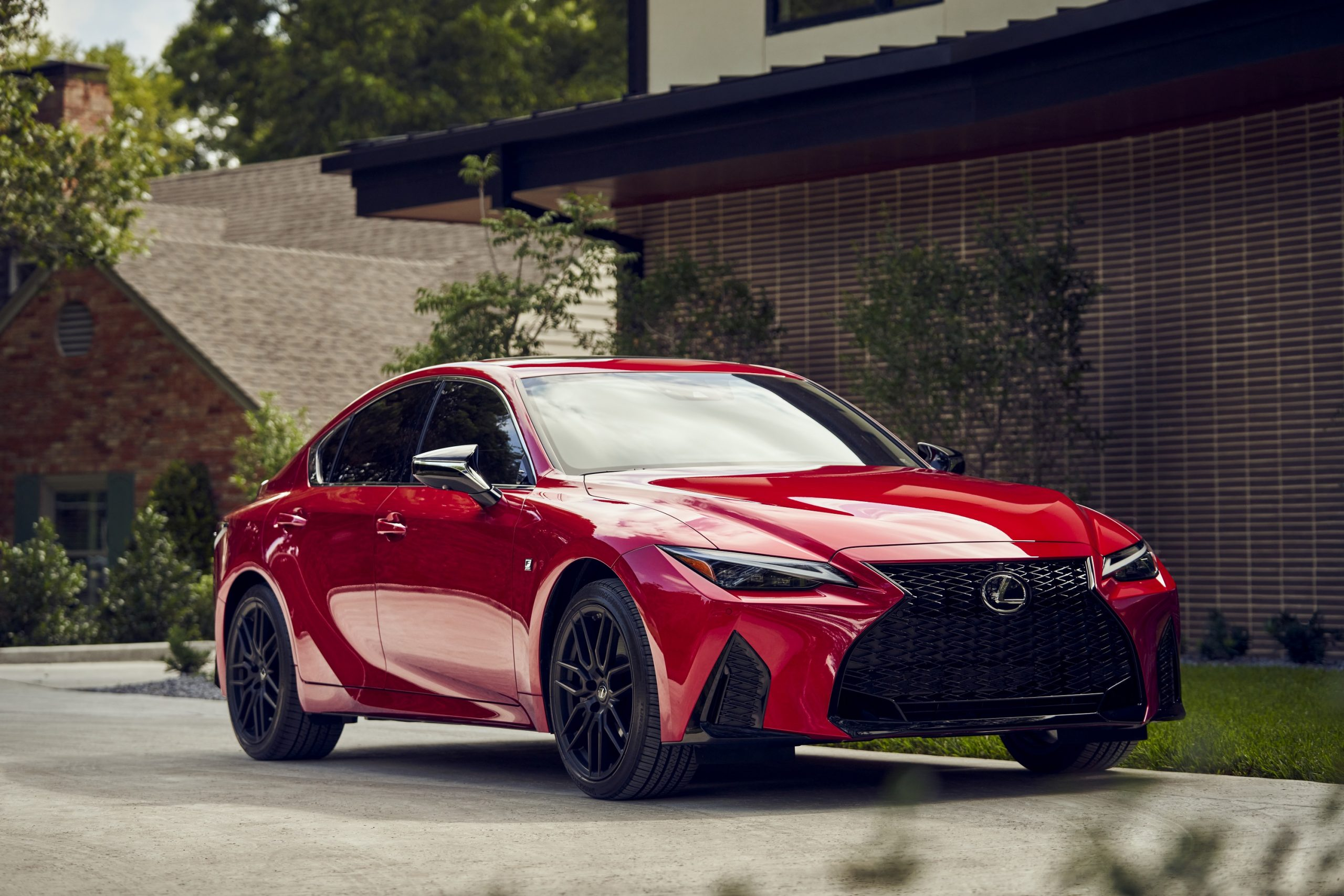 A red Lexus IS F-Sport shot from the front 3/4 in a residential area