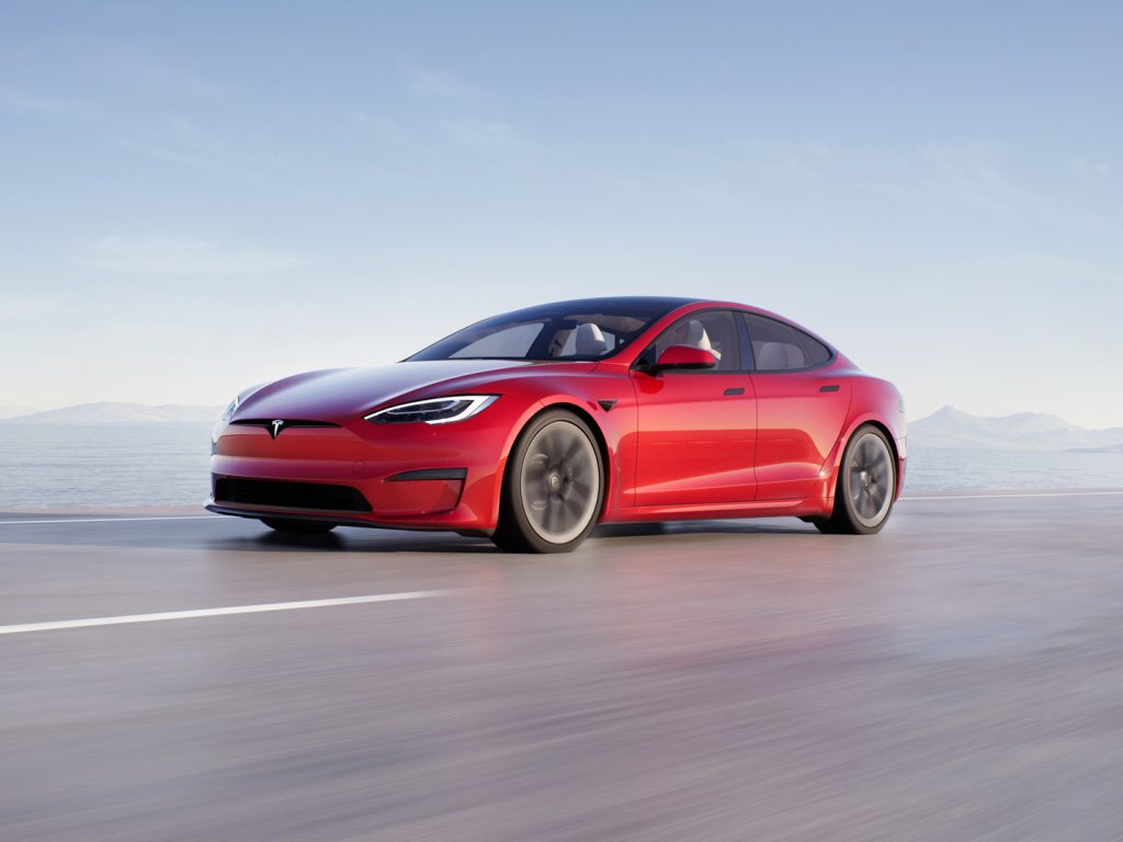 A red Tesla Model S Plaid, shot from a roll at the low front 3/4 angle