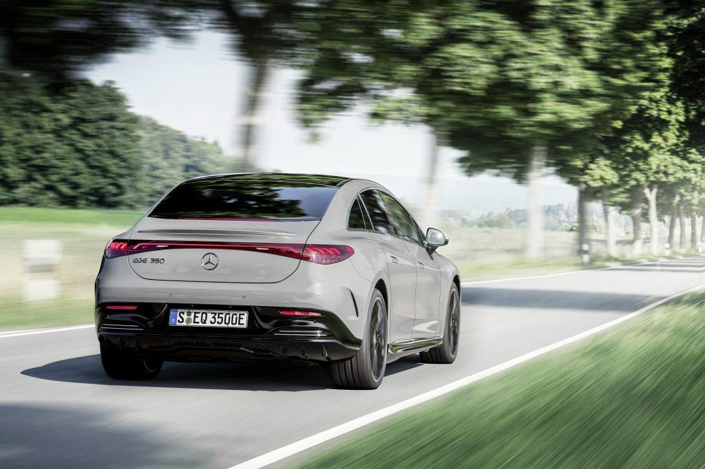 A steel-grey 2023 Mercedes-Benz EQE blasts down a shady back road