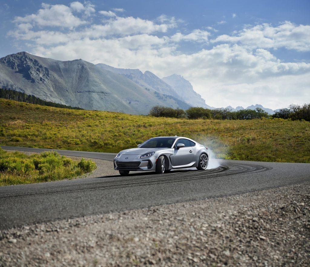 A silver 2022 Subaru BRZ slides it's way down a mountain pass kicking out tire smoke