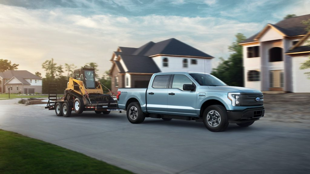 Blue 2022 Ford F-150 Lightning Pro towing a trailer. Pre-production model with available features shown. Available starting spring 2022. Max towing varies based on cargo, vehicle configuration, accessories and number of passengers.