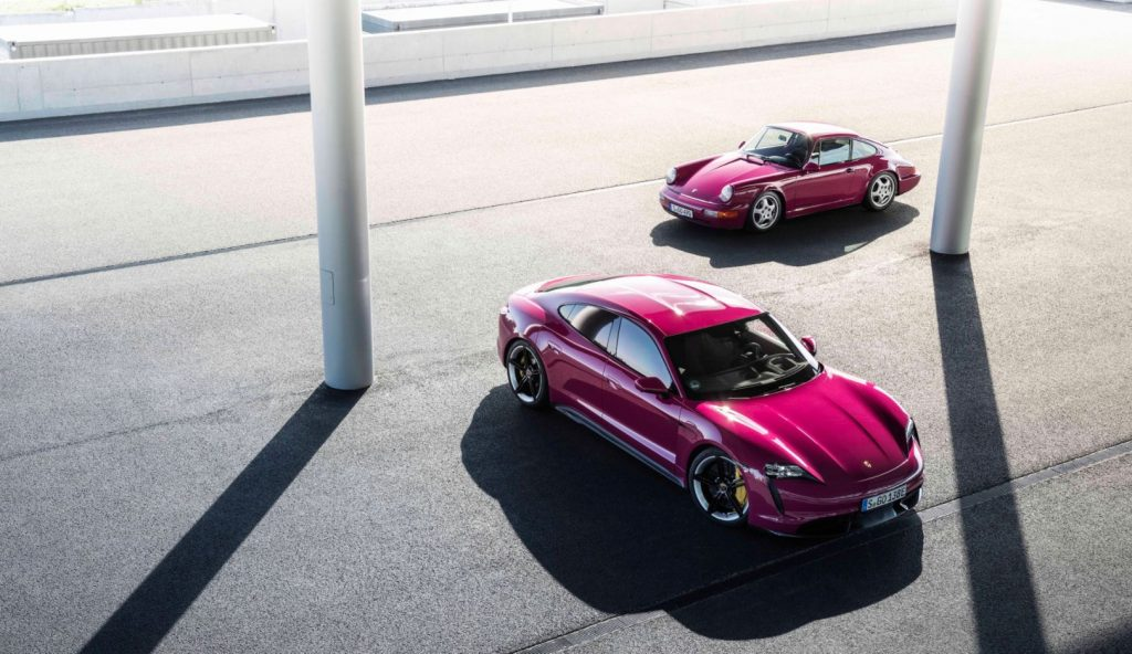 Two hot pink 2022 Porsche Taycans parked in an empty lot.