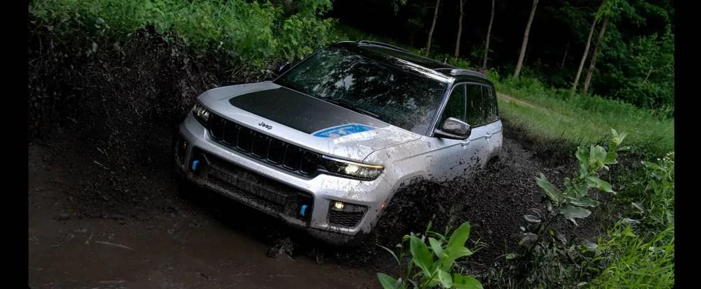 A white 2022 Jeep Grand Cherokee 4xe splashing through the mud.