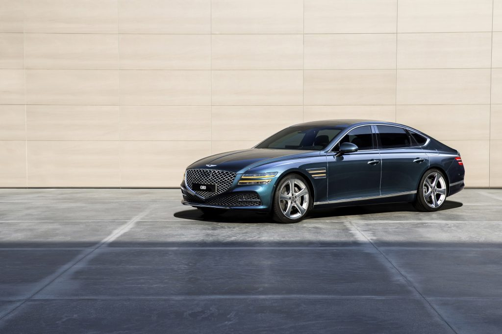 A forest green 2021 Genesis G80 luxury sedan photographed from the front 3/4 angle