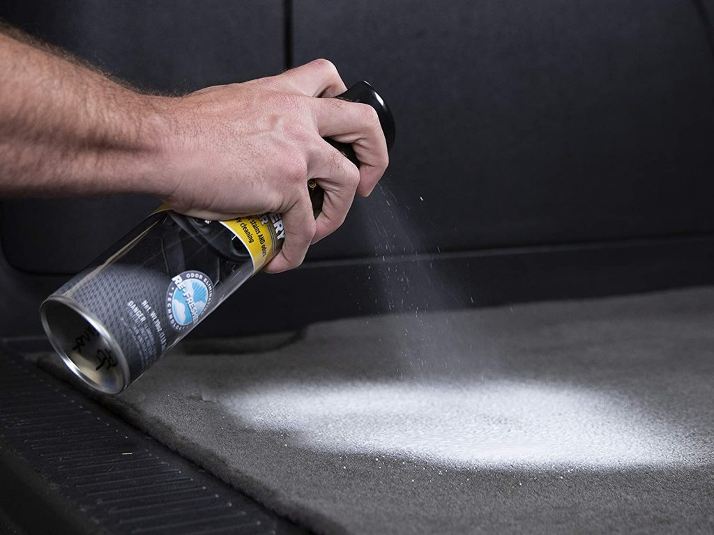 A man sprays upholstery cleaner onto a carpet, with the cleaner foaming on the mat