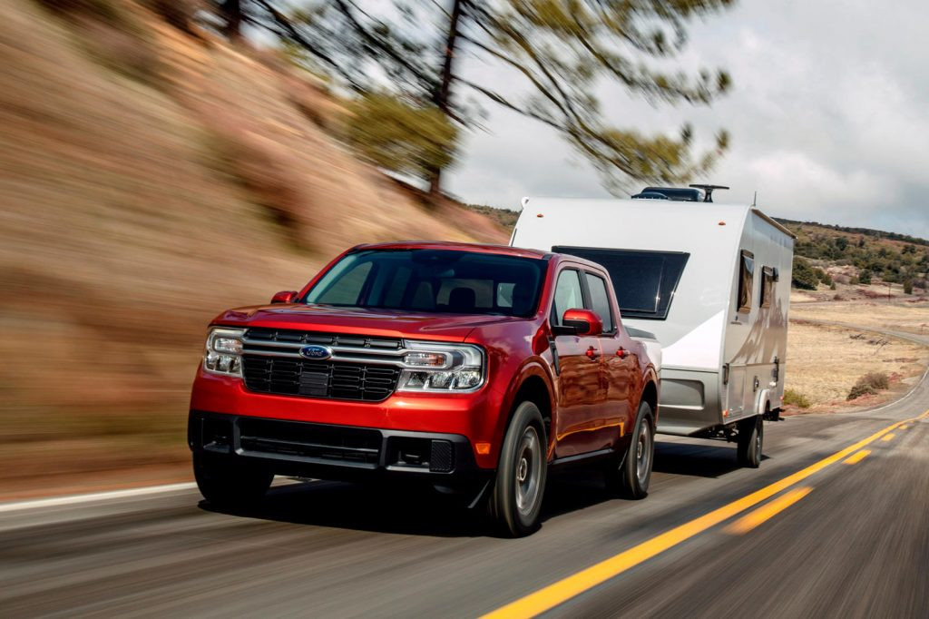 A red 2022 Ford Maverick towing a camper