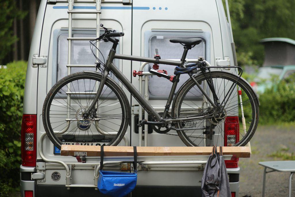 A white German RV with a gray bicycle on its ladder-mounted rack