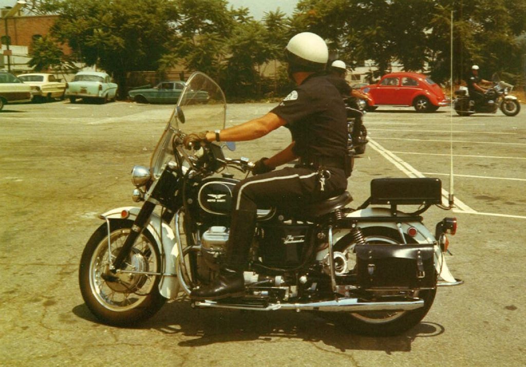 A Los Angeles police officer on a black-and-white Moto Guzzi Eldorado 850 police bike in a 1970s parking lot