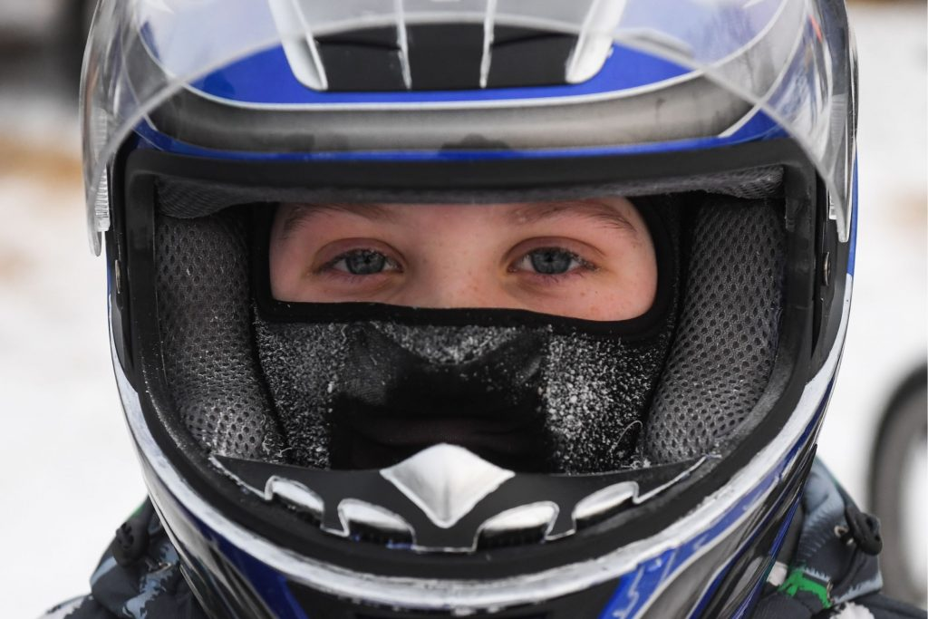 A Moto Skijoring competitor with a winter balaclava under their motorcycle helmet